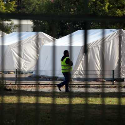 Bild: Flüchtling und Sicherheitsmann in einer Zeltstadt, über dts Nachrichtenagentur
