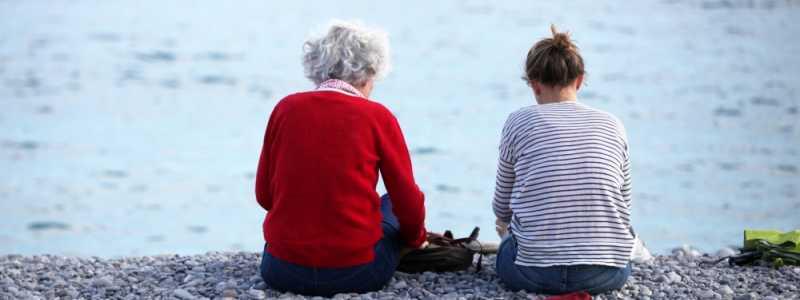 Bild: Alte und junge Frau sitzen am Strand, über dts Nachrichtenagentur